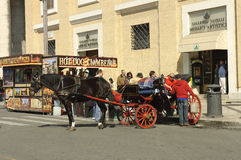 Carriage driver lifestyle in Rome. Carriage driver paying worker who collects horse detritus near an hot dog stand , Rome, Italy Royalty Free Stock Photos