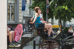Carriage. GHENT, BELGIUM - JULY 3, 2015: Two young women enjoy mounted on a carriage, which runs through the city Royalty Free Stock Photography