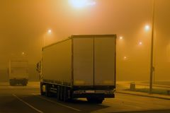 Carriage of goods by road, trucking industry - overweight vehicle, foggy night road. Carriage of goods by road, trucking industry - semi-trailer truck Stock Photos
