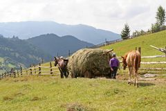 Carriage with hay on a background of mountains royalty free stock photography