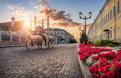 The carriage and horse rides on the pavement. Of the Kazan Kremlin in the sunshine sunset Stock Images