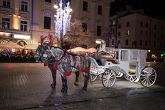 A carriage with horses. Christmas square. Krakow. Celebration. Night fair. Feast of approaching stock image