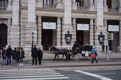 The carriage with horses rides past the Burgtheater in Vienna. Passers-by stand at the traffic lights. royalty free stock photos