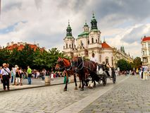 Carriage with horses and St. Nicholas church in the Old Town Square in Prague, Czech Republic. Carriage with horses and St. Nicholas church in the Old Town Royalty Free Stock Images