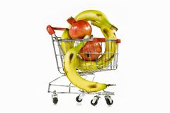 The carriage and pomegranates. Composition from yellow a banana and red a banana in the carriage from a supermarket royalty free stock photo