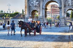 Carriage transport tourists along Via Dei Fori Imperiali near the  famous Arch of Constantine. Rome, Italy - June 30, 2018:Carriage transport tourists along Via Stock Photo