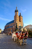 Carriages for riding tourists on the background of Mariacki cathedral Stock Photography