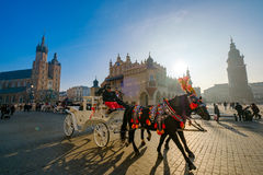 Carriages for riding tourists on the background of Mariacki cathedral. Krakow, Poland - December 20, 2016: Carriages for riding tourists on the background of Stock Photography
