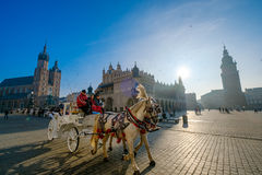 Carriages for riding tourists on the background of Mariacki cathedral. Krakow, Poland - December 20, 2016: Carriages for riding tourists on the background of Stock Image
