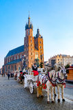 Carriages for riding tourists on the background of Mariacki cathedral Royalty Free Stock Image