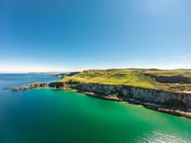 Carrick a Rede Rope Bridge in Ballintoy Northern Ireland. Aerial view on Cliffs and turquoise Atlantic Ocean water. Carrick a Rede Rope Bridge in Ballintoy royalty free stock photo