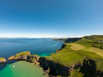 Carrick a Rede Rope Bridge in Ballintoy Northern Ireland. Aerial view on Cliffs and turquoise Atlantic Ocean water. Carrick a Rede Rope Bridge in Ballintoy royalty free stock images