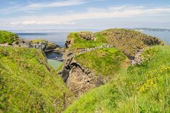 The Carrick-a-Rede rope bridge on the north Antrim coast, Northern Ireland on a sunny day. From a cleft in the cliffs, a view of Carrick-a-Rede rope bridge on royalty free stock photo