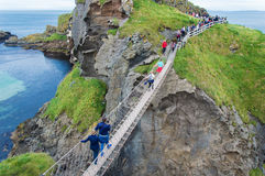 Carrick-a-rede Rope Bridge. People crossing the Carrick-a-rede Rope Bridge in County Antrim, Northern Ireland royalty free stock images