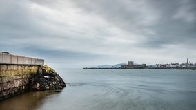 Carrickfergus Castle from Fishermans Quay. A seascape view of Carrickfergus town from Fisherman`s Quay and Downshire Beach royalty free stock image