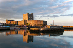 Carrickfergus Castle at sunset. Medieval Norman Castle in Carrickfergus, Northern Ireland, and its reflection in water at sunset Stock Image