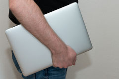 Male person carrying laptop. Body of a man carrying a laptop under his arm with a studio background Royalty Free Stock Photo