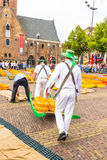 Carriers walking with many cheeses in the famous Dutch cheese market Stock Photos