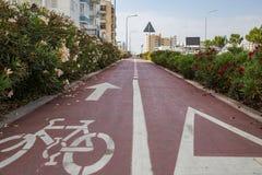 Carril de bicicleta, asfalto rojo con la flecha blanca para las bicis Paisaje urbano y fondo del cielo Imagen de archivo libre de regalías
