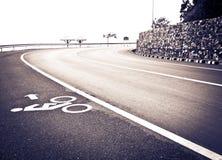 Carril de bicicleta en la calle del uphill&downhill con la muestra, fotografía de archivo