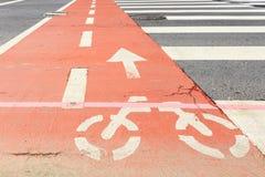 Carril de bicicleta y paso de cebra anaranjados Imagenes de archivo