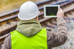 Carriles filmados ingeniero ferroviario con la tableta Imagen de archivo