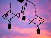 Carrilhão de vento dos peixes com por do sol roxo e alaranjado Imagens de Stock