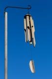 Carrilhões de vento de bambu contra um céu azul imagem de stock