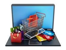 Carrinho de compras, cartões de crédito e sacos estando no laptop Fotos de Stock