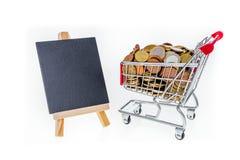 Carrinho de compras com as moedas de um centavo e o quadro preto a escrever sobre Iso Fotos de Stock
