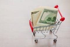 Carrinho de compras com dinheiro dos dólares no fundo de madeira Fotografia de Stock Royalty Free