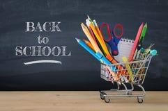 Carrinho de compras com fonte de escola na frente do quadro-negro De volta ao conceito da escola imagens de stock