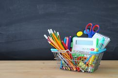 Carrinho de compras com fonte de escola na frente do quadro-negro De volta ao conceito da escola imagem de stock