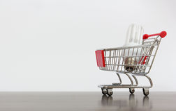 Carrinho de compras com lâmpada da economia Fotos de Stock