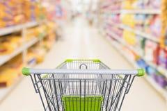 Carrinho de compras com a loja de disconto abstrata do supermercado do borrão fotos de stock