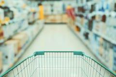 Carrinho de compras com o corredor da loja da eletrônica do borrão fotografia de stock royalty free