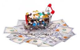Carrinho de compras completamente com comprimidos e cápsulas sobre notas de dólar Foto de Stock Royalty Free