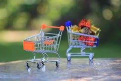 Carrinho de compras diminuto modelo no fundo verde, conceito em linha de compra imagem de stock