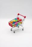 Carrinho de compras diminuto que contém bolas coloridas Fotos de Stock