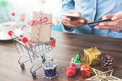Carrinho de compras e caixas de presente com as mãos que guardam o cartão de crédito e que usam o telefone celular, compra em lin Imagem de Stock