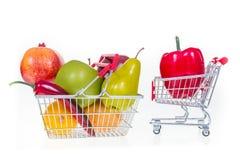 Carrinho de compras e cesto de compras completamente com frutas e legumes Foto de Stock Royalty Free