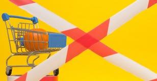 Carrinho de compras em que se encontram o mandarino, a fita proibida, o conceito das sanções na importação dos bens e os produtos imagens de stock royalty free