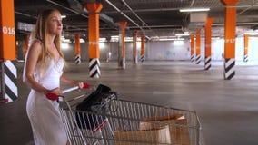 Carrinho de compras levando da mulher bonita no estacionamento video estoque