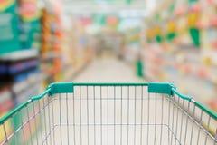 Carrinho de compras no corredor do supermercado e prateleiras no backgroun do borrão Imagens de Stock
