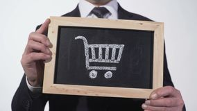 Carrinho de compras no quadro-negro nas mãos do homem de negócios, comércio a retalho, pacote do consumidor filme