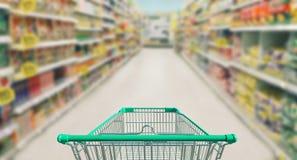 Carrinho de compras no supermercado e no backg borrado do bokeh da loja da foto imagem de stock royalty free