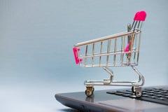 Carrinho de compras ou trole do supermercado com o caderno do portátil no gre Fotos de Stock