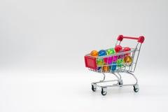 Carrinho de compras que contém bolas coloridas Fotografia de Stock Royalty Free