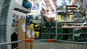 Carrinho de compras que move-se através dos corredores do supermercado de Domingo entre béns manufaturados filme