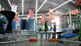 Carrinho de compras que move-se através dos corredores do supermercado de Domingo entre bens domésticos filme